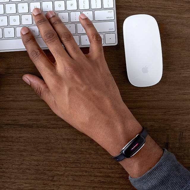 man wearing a bond touch bracelet while working on the computer
