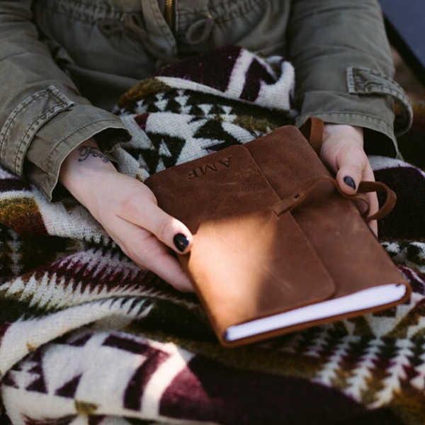 Woman holding a personalized brown leather journal