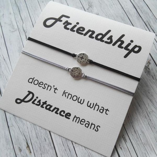 two long distance themed friendship bracelets wrapped around a card