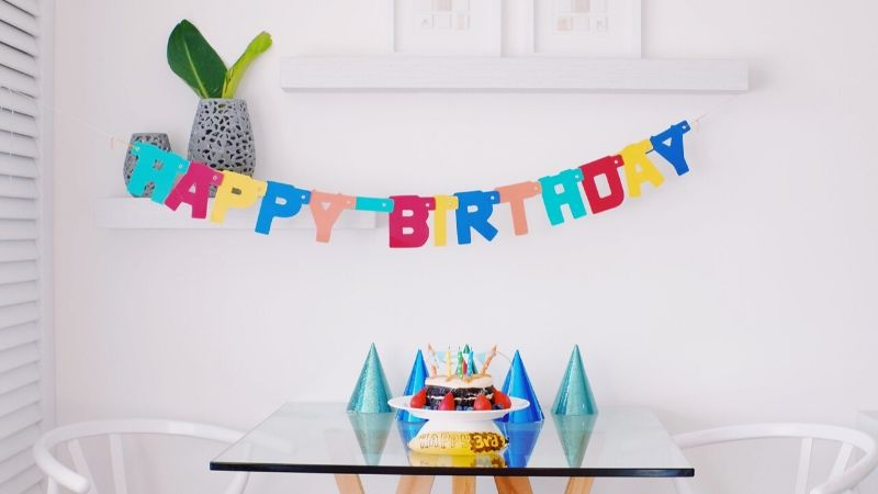 birthday with a sign, cake and party hats