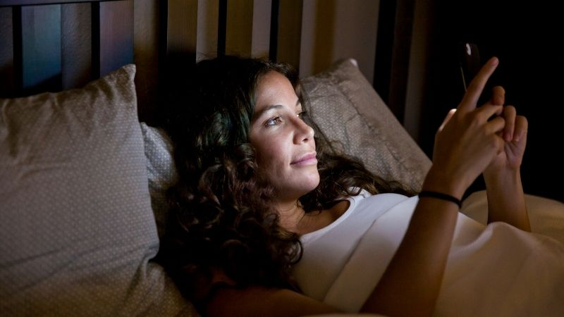 woman reading text messages on smartphone in bed at night