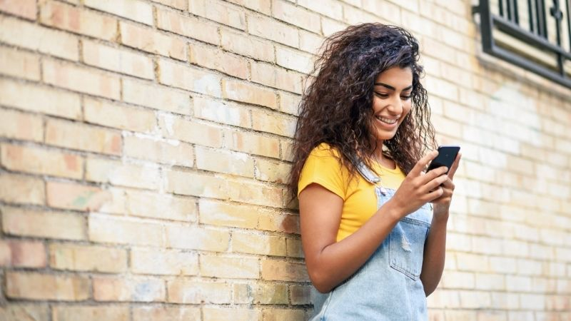 woman smiling and looking down at phone